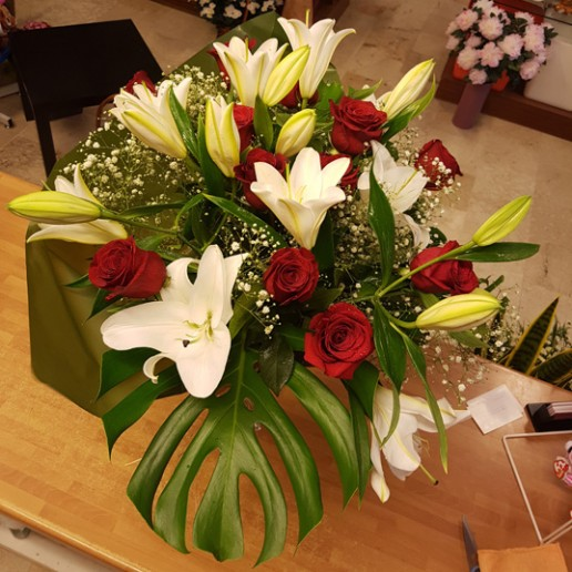 Ramo compuesto por 12 rosas rojas y orientales blancos